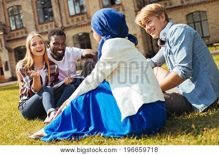 Cultural backgrounds. Young clever inventive woman helping new students adapting at the university while giving them some tips and establishing friendly relationships