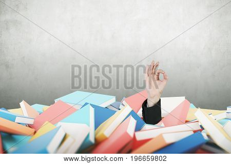 Hand of a man in a suit making on OK sign near a blank concrete wall. He is buried under a pile of book. Mock up