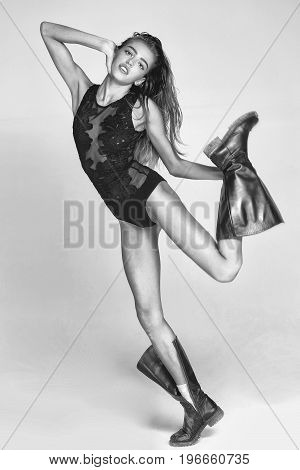 woman with long wet hair in bodysuit and dirty boot black and white
