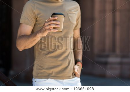 Close up of hands and body of young man standing outside old building. He is holding cup of coffee in hand