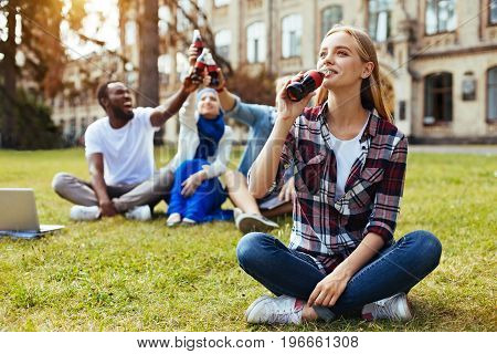 So tasty. Energetic gorgeous young lady taking a sip from the bottle while feeling thirsty enjoying warm weather outdoors