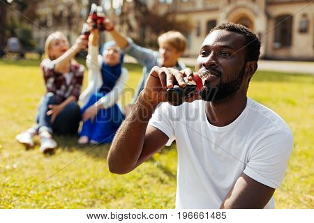 Cool drink. Energetic dynamic handsome man sitting on the grass and taking a sip from the bottle while enjoying refreshing drink