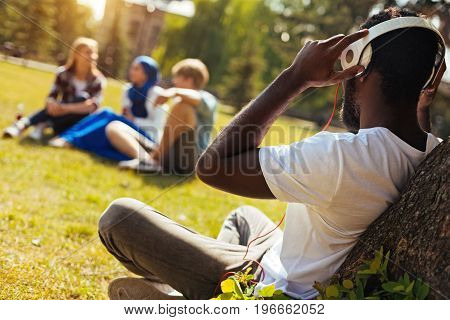 Relaxing hobby. Lively wonderful creative man sitting under the tree and wearing headphones while playing his favorite songs