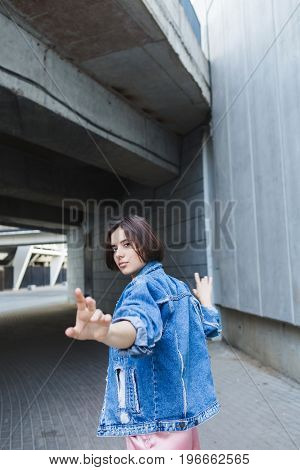 A stylish brunette woman with short hair in pink sports shorts white top and denim jacket. Woman in pink sporty look. Woman dancing