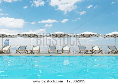 White deck chairs are standing under beach umbrellas near a swimming pool. A blue sky with clouds is above them. 3d rendering mock up