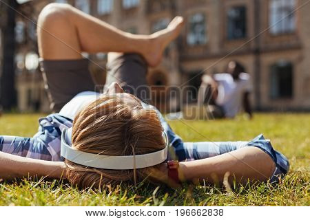 Escaping the buzz. Young clever easy going man taking a moment for relaxing after a long day at the university while lying on the grass