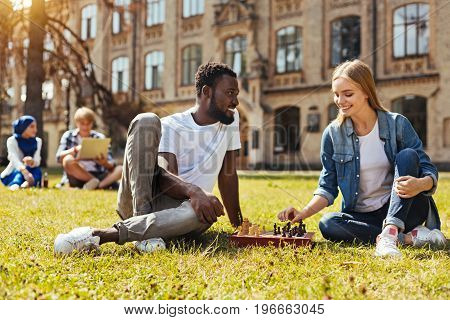 Sport for intellectuals. Positive open minded clever woman making her move while sitting on the grass and meeting for match with her friend