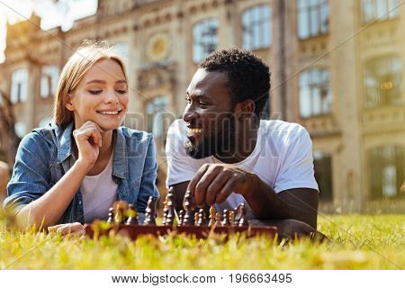 Looking for a chance. Intelligent charming nice lady being very focused while playing chess with her friend and learning about his strategy