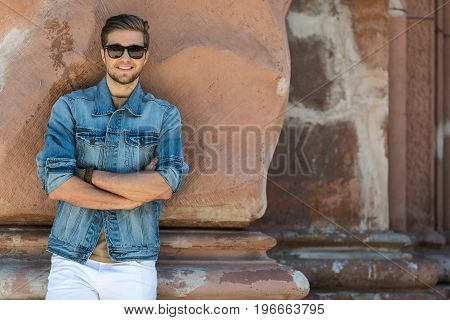 Waist up portrait of happy bearded man in sunglasses standing near ancient building. He is leaning on uneven wall with folded arms and smiling. Copy space in right side