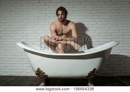 bathroom and home comfort. spa and relaxation. hygiene and healthcare. man with muscular body in bath. guy sitting in bath tub.