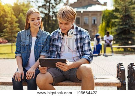 Unconventional workplace. Young passionate productive student meeting his friend at the university and showing her something using his tablet