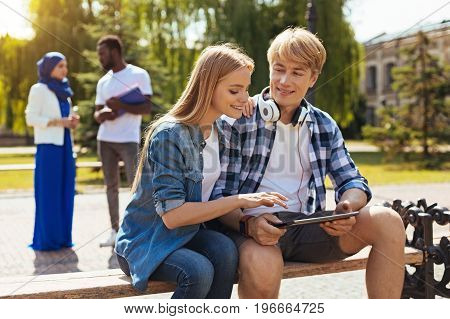 Adding alternations. Savvy attentive charismatic lady discussing something with her fellow student while he sharing his ideas and showing them on his tablet