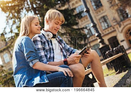 Perusing the list. Attentive intelligent motivated sitting on a bench with her friend and looking at the screen while he showing her something