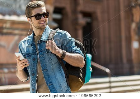 Waist up portrait of happy young bearded guy in sunglasses. He is strolling down city street with backpack and listening to music via cellphone. Copy space in right side