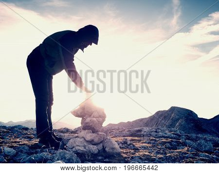 Man Hiker Is Building Pebbles Pyramid. Stones On Alps Mountain Summit. Daybreak Horizon