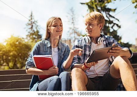 Managing the ideas. Lively smart wonderful lady meeting her fellow student for giving him some tips on how they needing developing their assignment