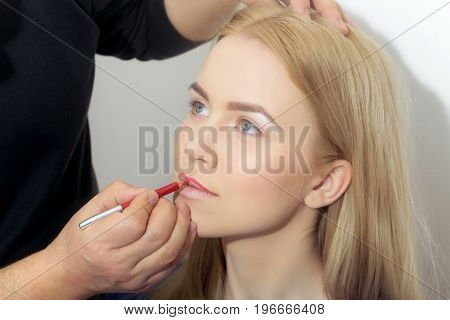 Hand Of Visagiste Applying Red Pencil On Woman Lips