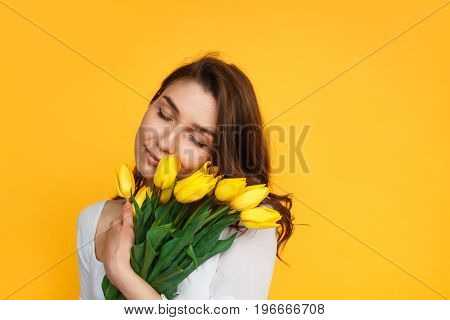 Yong brunette with eyes closed embracing bunch of yellow tulips on yellow.