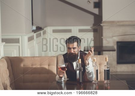 Man Sitting On Sofa With Martini Glass And Three Bottles