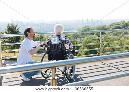 How can I help you. Dedicated observant nice guy asking senior lady how she feeling while working as a volunteer and taking care of her