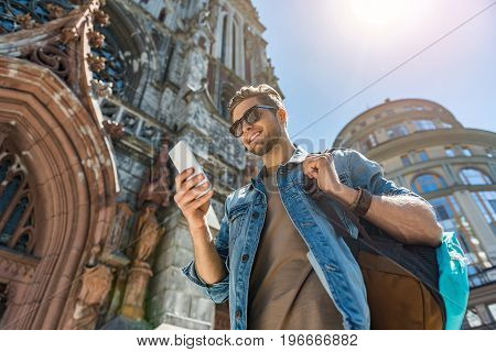 Waist up portrait of happy youthful bearded guy in sunglasses standing by old gothic building. He is looking at his mobile phone and smiling. Low angle