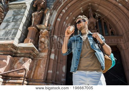 Portrait of jolly young bearded man in sunglasses is standing back to huge gothic arch of old historical building. He is drinking coffee and holding backpack. Copy space in left side. Low angle