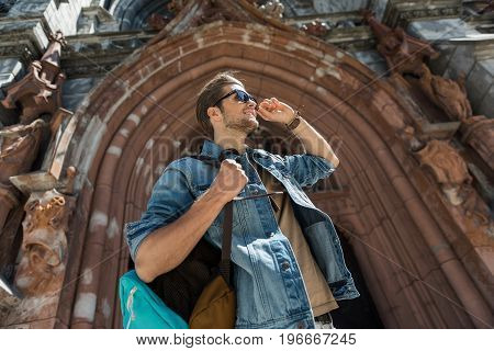 Cheerful young bearded man is standing in center of gothic arch of old castle. He is carrying backpack and touching sunglasses. Low angle