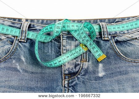 Healthy Lifestyle And Dieting Concept: Measure Tape Fastened Around Jeans