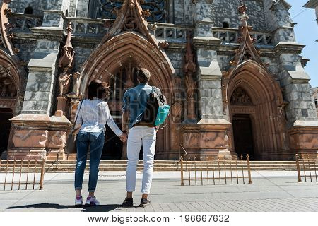 Youthful man and woman standing in front of high medieval building. They are holding hands and facing huge gothic arches. Copy space in right side. Focus on back