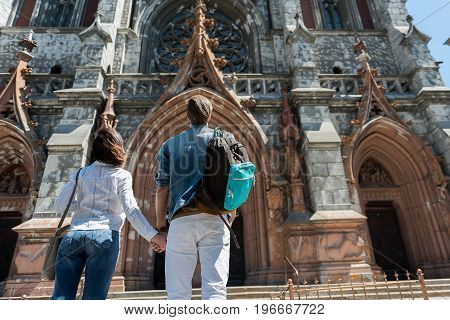 Low angle of young couple looking at beautiful medieval castle. They are holding hands and carrying bags. Copy space in right side