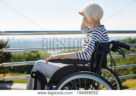 Too bright to see. Focused curious elderly lady covering her eyes from the sun while enjoying the city skyline and sitting in a wheelchair