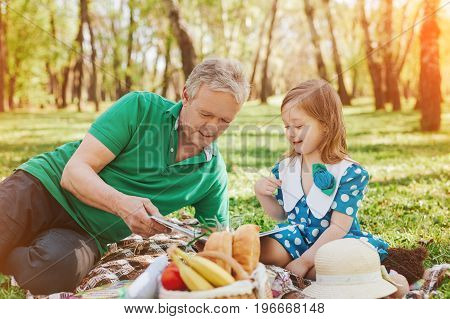 Elderly man and little girl sitting on plaid with basket of food and reading book in park.