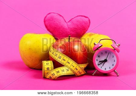 Apples of different colors wrapped with yellow flexible ruler pink toy heart standing up on them and pink retro alarm clock placed nearby isolated on light pink background. Concept of love to diets