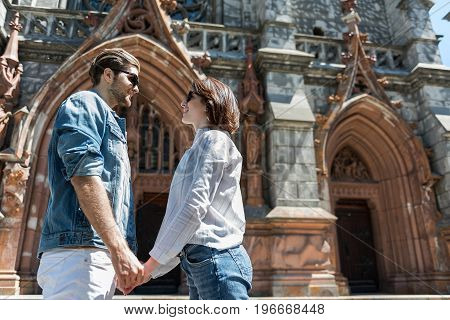 Low angle of happy youthful man with beard and woman standing near old gothic building and holding hands. They are gazing at each other through sunglasses and smiling. Copy space in right side