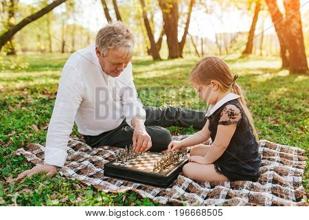Mature man sitting on plaid in park with little girl playing chess