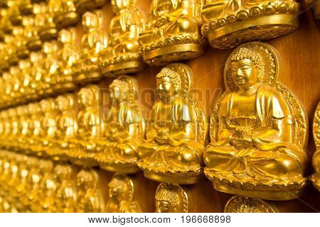 Many small Buddha statue on the wall at chinese temple, Thailand
