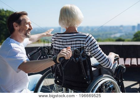 You can do anything. Humorous imaginative king volunteer entertaining elderly lady while telling her stories and taking her for a walk