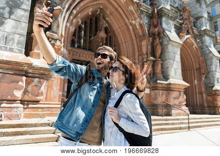 Happy young woman and bearded man are taking selfie photo near old gothic style building. They are wearing sunglasses and smiling