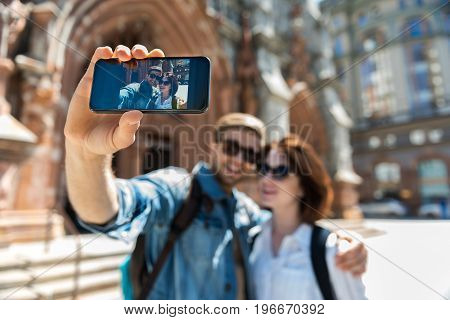 Happy young couple in sunglasses is standing on street beside old building. Man with beard is hugging girl by shoulder and taking photo of themselves. Focus on gadget with picture