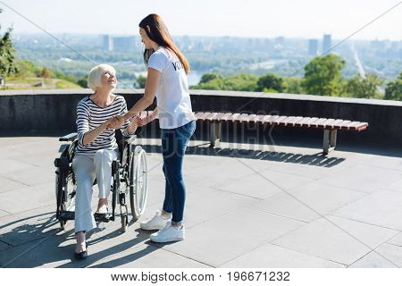 What would I do without you. Energetic optimistic aged woman looking delighted while trying standing up from a wheelchair and being assured by the young woman
