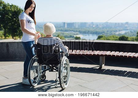 I am here for you. Admirable kind charming woman supporting elderly lady and holding her by the hand while assisting he on a daily basis