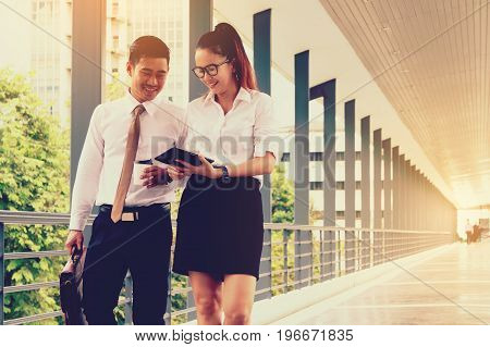 Two asian business walking for the way and looking finance data analyzing on tablet screen.