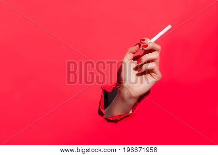 Anonymous hand holding cigarette in torn hole of red paper.