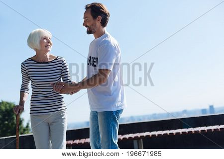 I can walk a mile with you. Pretty adorable aged woman having an active lifestyle and asking the volunteer escorting her while she making her daily promenade