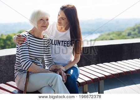 Dreamy mood. Elegant inspired calm lady enjoying perfect weather outdoors while young girl taking care of her and taking a daily stroll with her