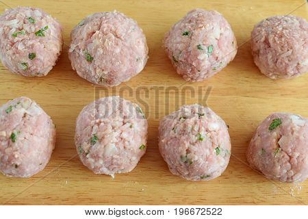 Raw beef meatballs with mint and rice on a wooden cutting board. Step by step cooking. Traditional greek food