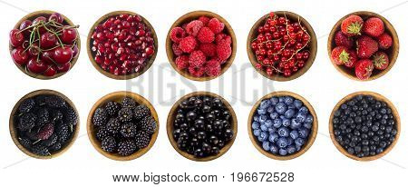 Black-blue and red berries isolated on white background. Collage of different fruits and berries. Blueberry mulberry bilberry blackberries cherry strawberry currant pomegranate and raspberry. Collection of fruits and berries in a bowl. Top view.