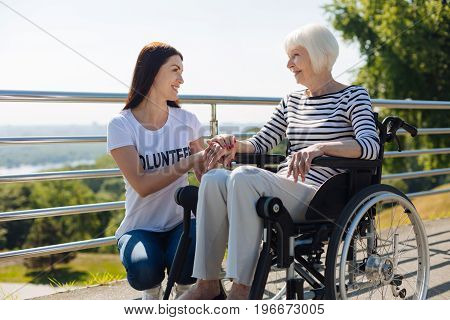 You are my wonder. Graceful pretty aged lady talking to a young woman while assisting her and taking care of all she needing at the moment
