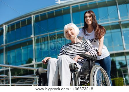 Movement is life. Outgoing romantic remarkable lady enjoying sunny weather and sitting in a wheelchair while young woman helping her talking a stroll