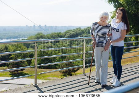 Take it easy. Motivated genuine attentive lady holding senior woman by the hand and helping her taking a stroll while she having some troubles with her leg